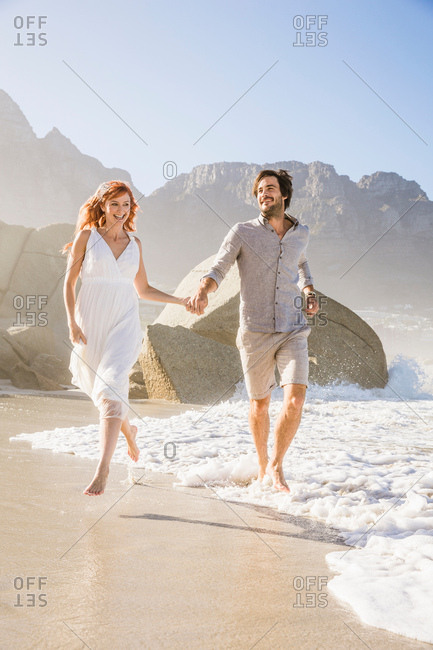 Full length front view of couple running on beach holding hands