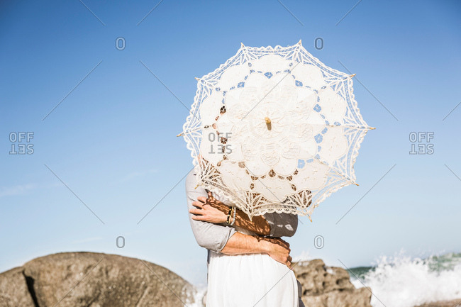 Couple on beach hugging obscured by lace umbrella