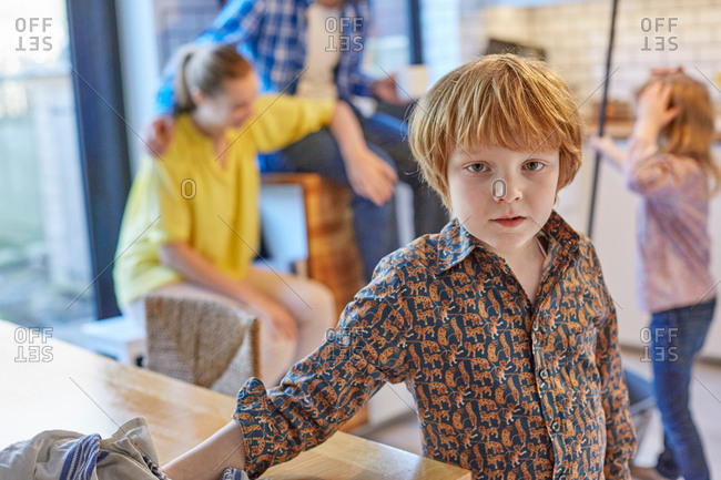 Boy wiping dining table, people in background