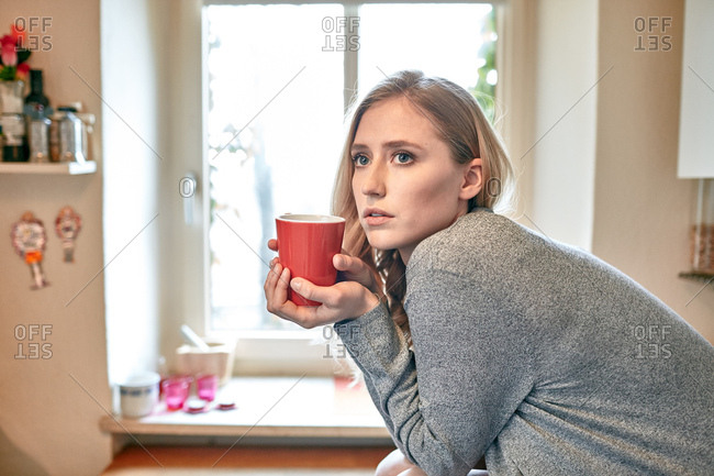 Young woman leaning forward on kitchen counter with cup of coffee