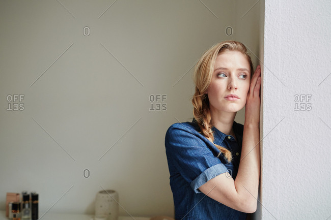 Beautiful young woman with blond plait leaning against door