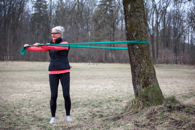 Mature female training in park, pulling resistance band