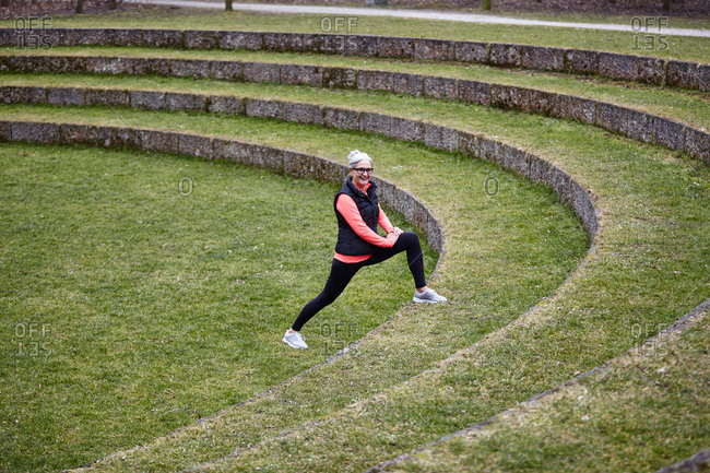 Mature female training in park, stretching legs on grass stairway