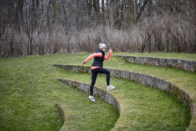Mature female training in park, running up grass stairway