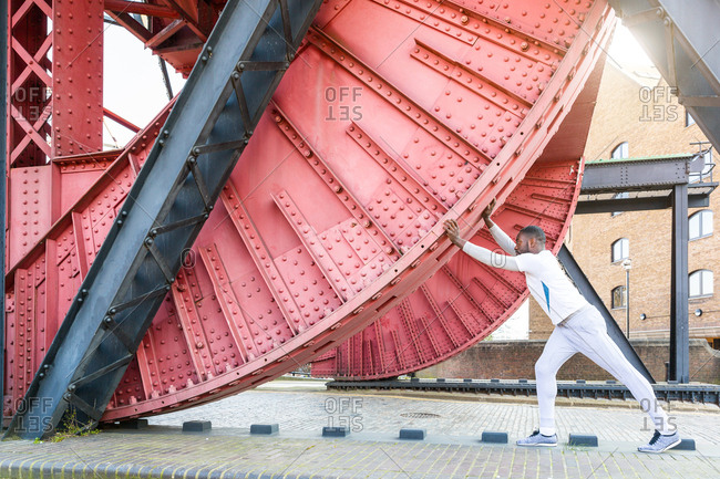 Mid adult man exercising in urban environment, stretching against metal structure