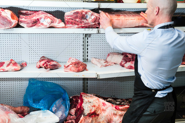 Butcher placing joint of meat on refrigerated cabinet, rear view