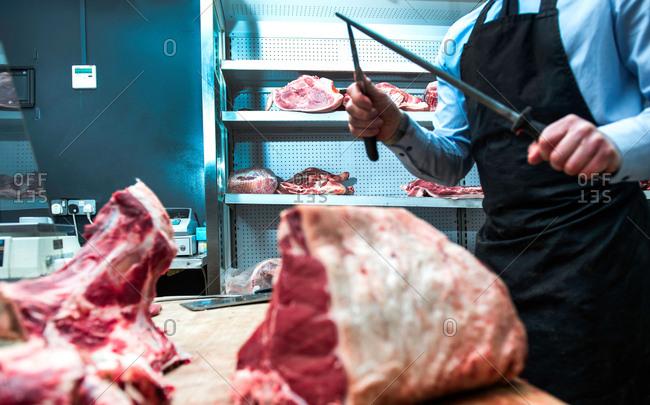 Butcher sharpening knife on knife steel in butcher's shop, mid section
