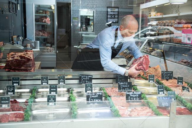 Butcher preparing window display in butcher's shop