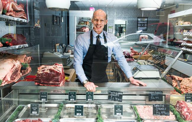 Portrait of butcher, through shop window