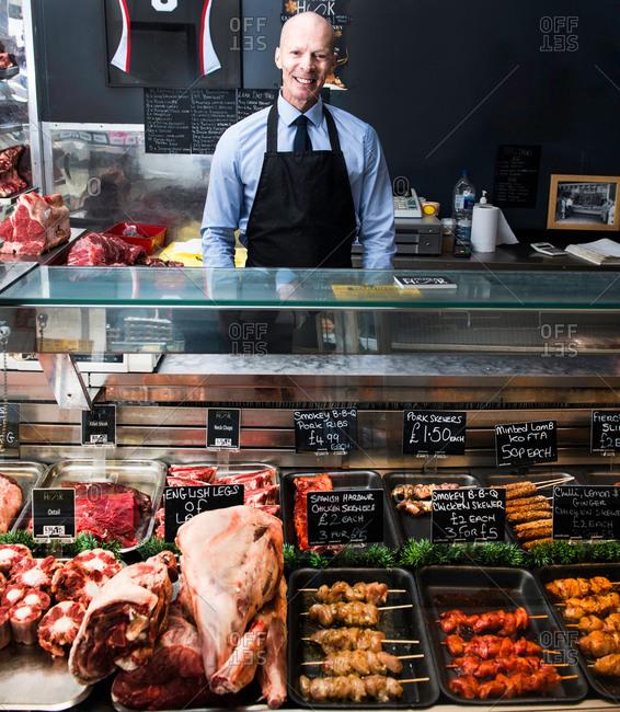 Portrait of butcher, standing behind counter