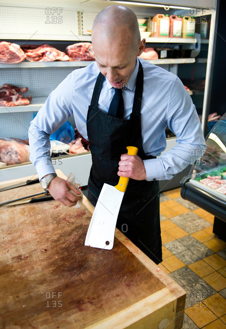 Butcher cleaning meat cleaver in butcher's shop