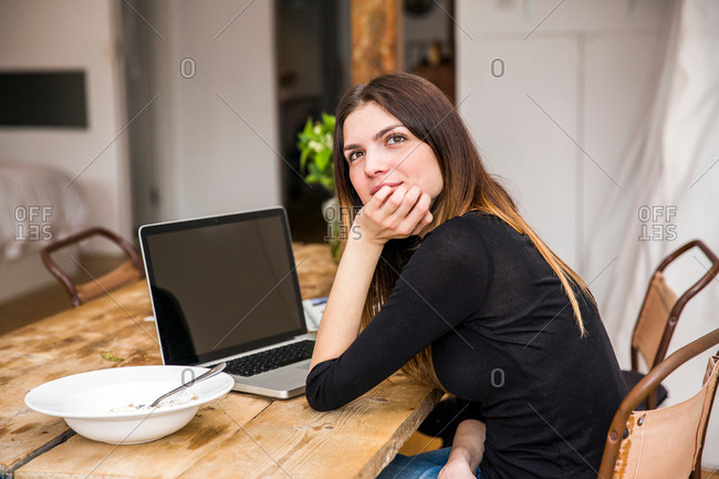 Young woman in apartment daydreaming at table with breakfast and laptop