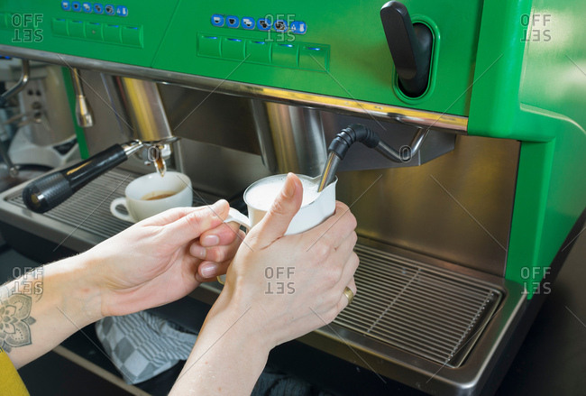 Hand of tattooed waitress preparing cappuccino on cafe coffee machine