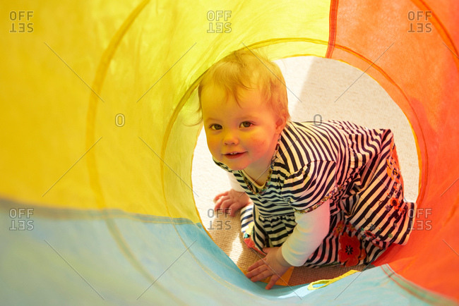Portrait of baby girl crawling in multi-color tunnel