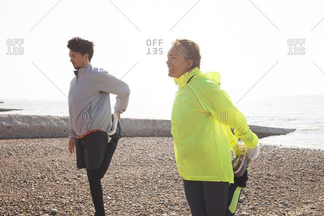 Man and woman training, standing on one leg on Brighton beach