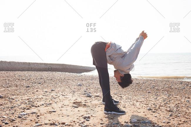 Young man training, bending forward on Brighton beach