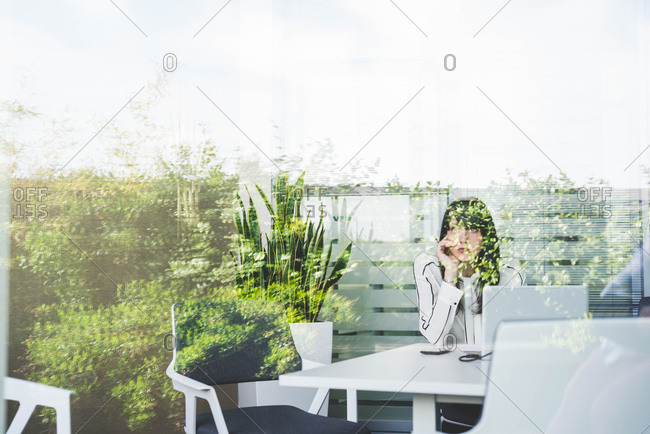 Window view of businesswoman gazing through window from office desk