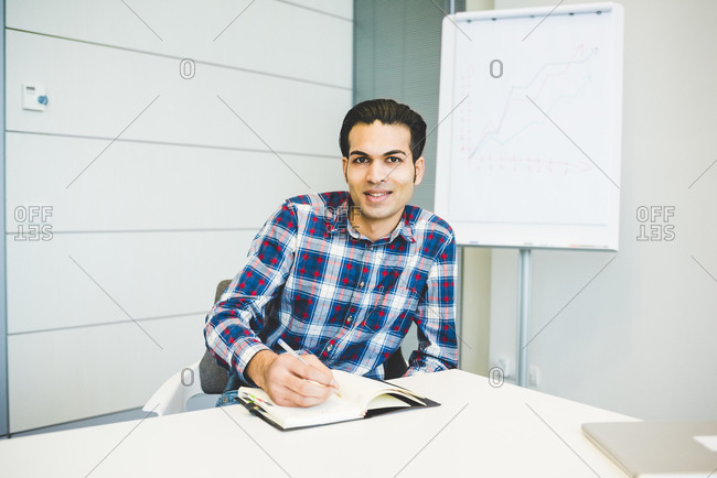 Portrait of young male designer working on notebook in office