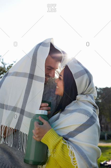 Couple wrapped in blanket holding drinks flask face to face smiling