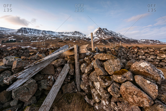 Dry stone wall and snow covered mountains, Reykjavik, Iceland