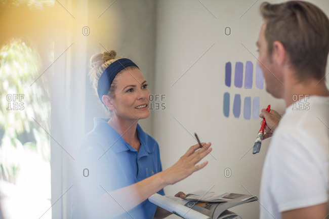 Couple holding brochure discussing paint colors on wall