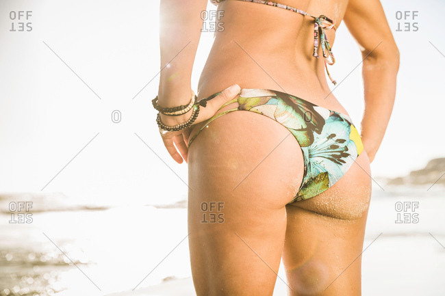 Neck down rear view of mid woman wearing bikini on beach, Cape Town, South Africa