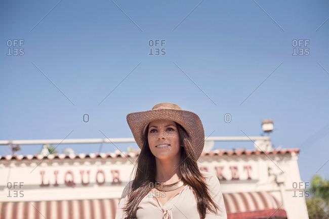 Female tourist outside liquor store, Los Angeles, California, USA