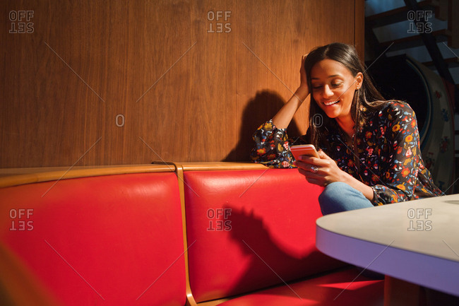 Woman sitting in wood panelled booth looking down at smartphone smiling