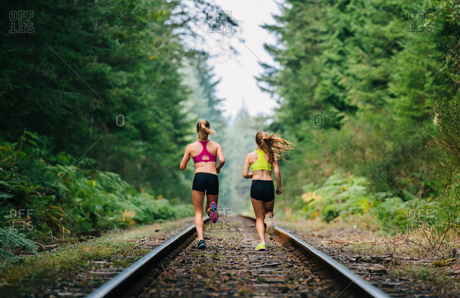 Young woman and teenage girl running on rural train track, rear view