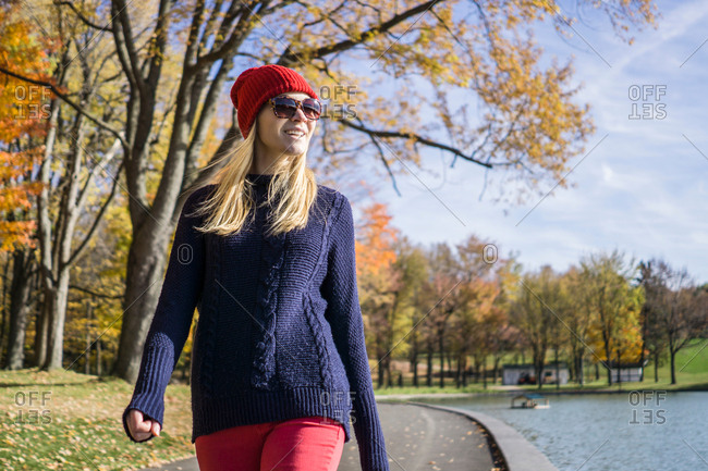Stylish young woman wearing red knitted hat strolling in park