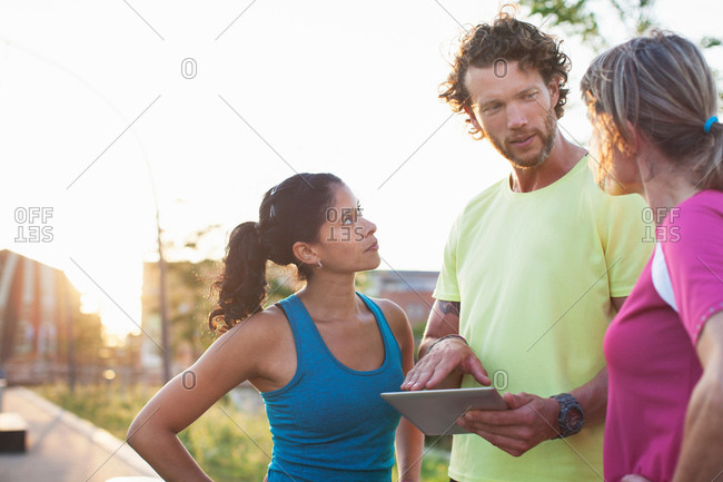 Male personal trainer and two women updating digital tablet at riverside