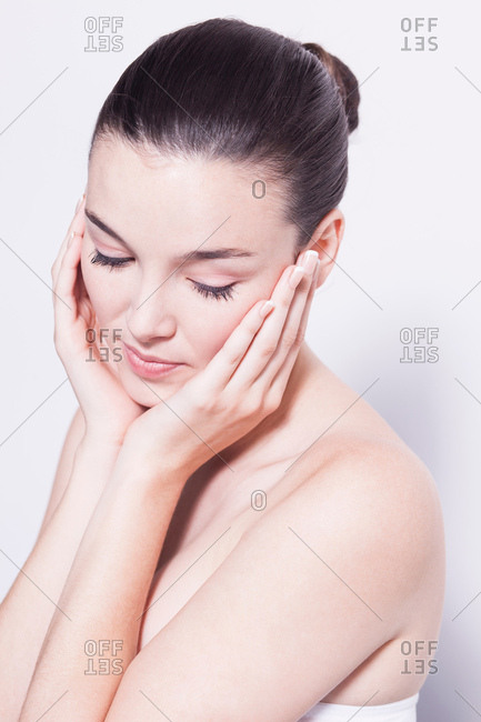 Head and shoulder shot of beautiful young woman with hands on cheeks