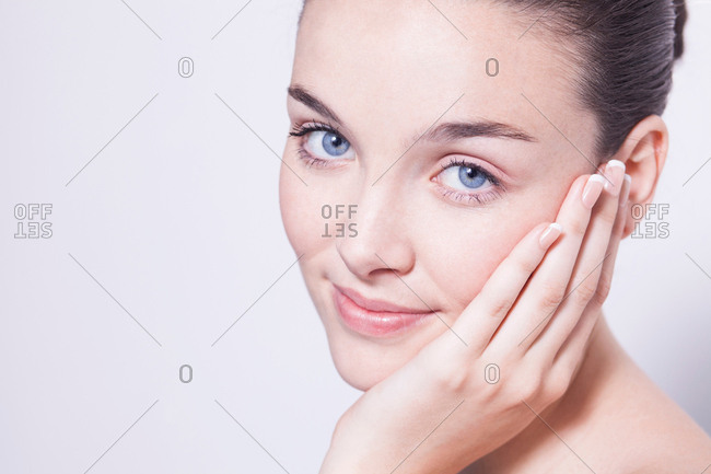 Portrait of beautiful young woman with hands on cheek
