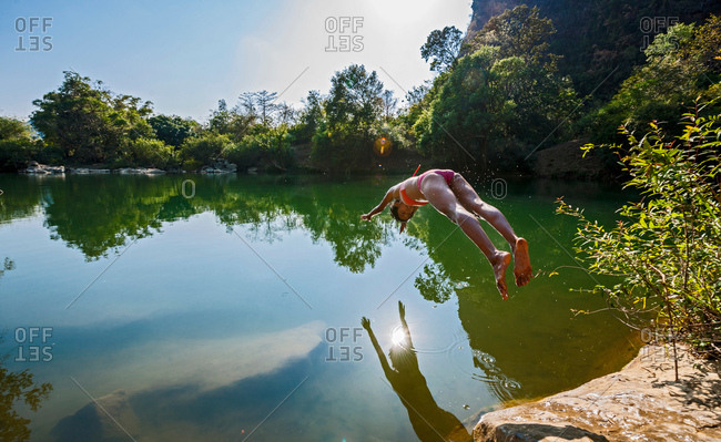 Young woman diving into Thafalang River, Thakhek, Khammouane, Laos