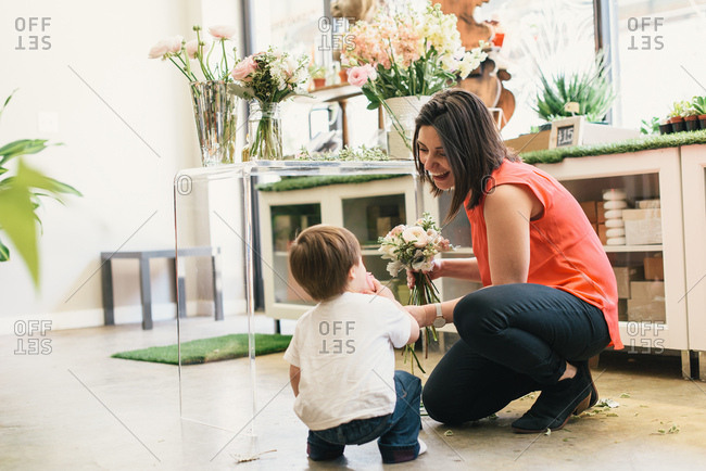 Mother crouching with son in flower shop, mother holding bouquet