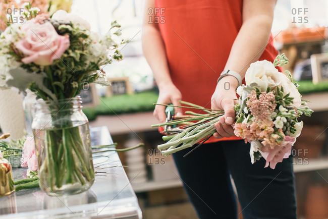 Florist arranging bouquet in flower shop, mid section