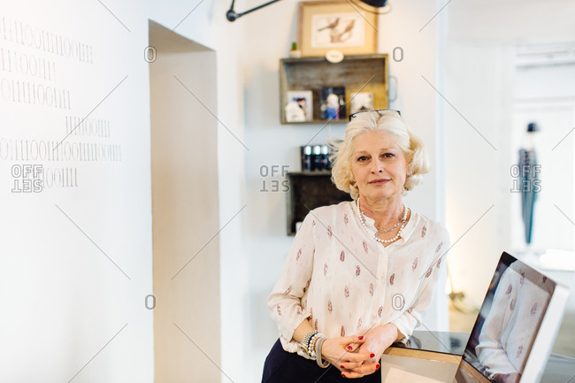 Small business owner leaning against counter looking at camera