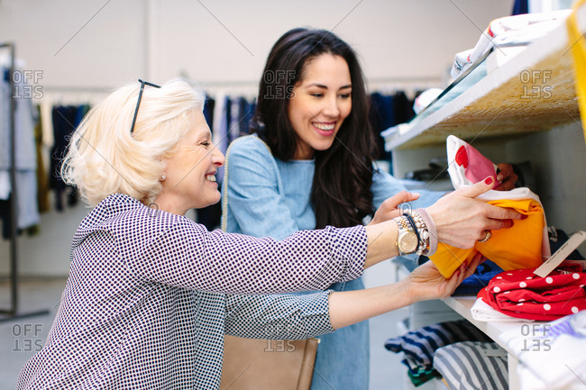 Women in clothes shop looking at folded t-shirts smiling