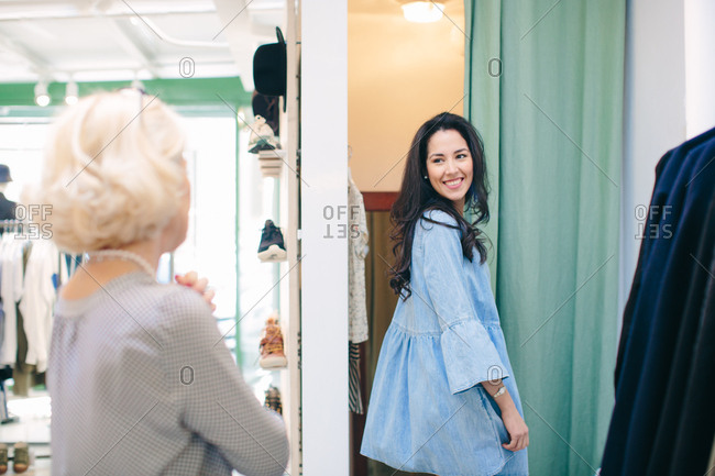 Woman in clothes shop changing room looking over shoulder at friend smiling