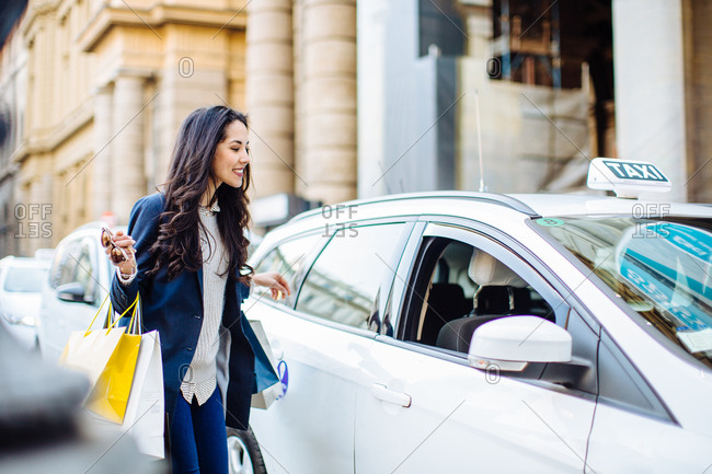 Woman carrying shopping bags hailing a taxicab