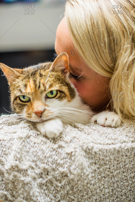 Over the shoulder of woman nuzzling cat
