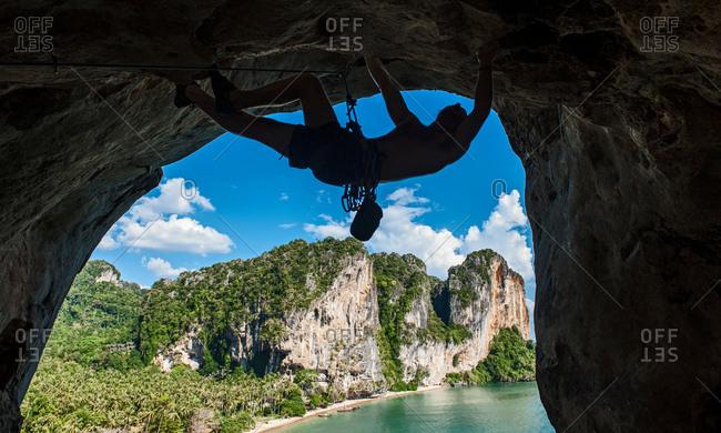 Silhouette of rock climber climbing on Burnt Offerings, Tonsai, Railway Beach, Krabi, Thailand