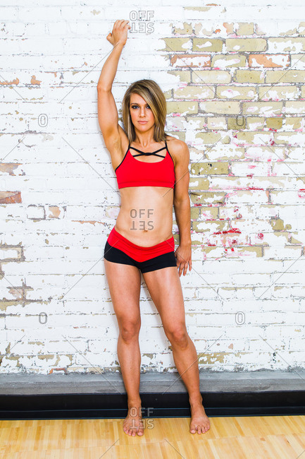 Young woman wearing a sports bra standing with her arm up