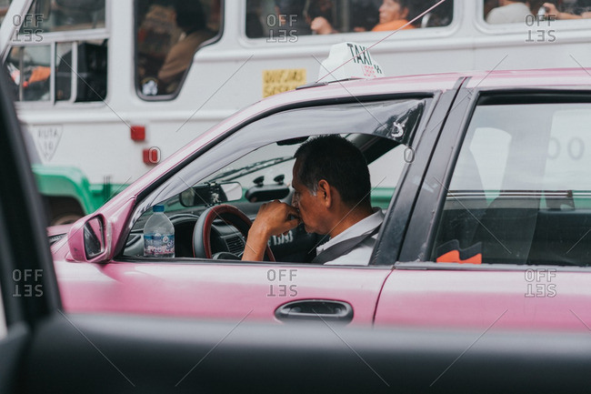 Mexico City, Mexico - August 11, 2016: Taxi driver stopped in traffic with his window rolled down