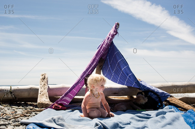 Toddler sitting on a blanket at the beach shaded by a lean-to