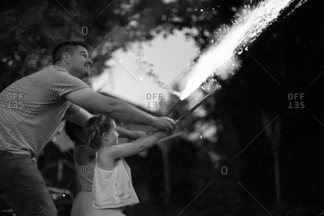 Father shooting fireworks with his children