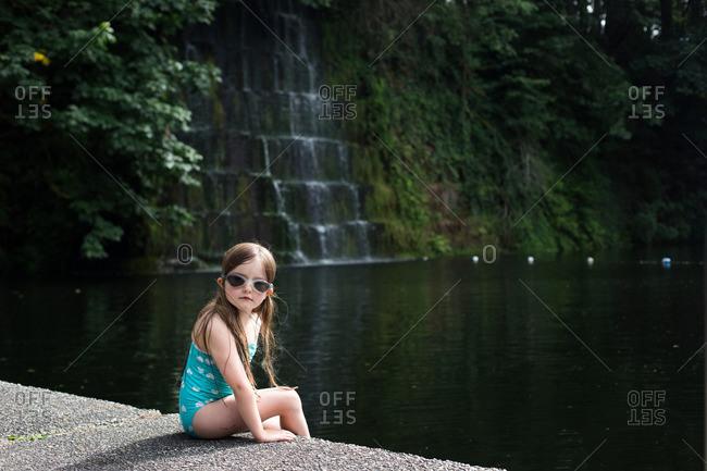 Girl sitting on stone embankment along a lake