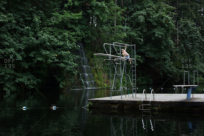 Boy climbing a high dive at a secluded swimming hole