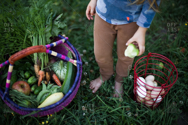 Girl standing outside next to a basket of eggs and a basket of fruits and veggies