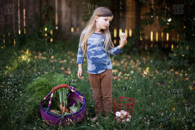 Young girl standing outside next to a basket of eggs and a basket of fruits and veggies